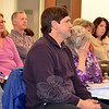 Sandy Hook resident Susan Oberstadt holds her head in her hand as she sits beside her son, Michael, listening to neighbors criticize the idea of the town taking her childhood home by eminent domain during a Legislative Council meeting December 18. The council later unanimously rejected the idea of taking the property to build a new driveway for Sandy Hook School. (Voket photo)