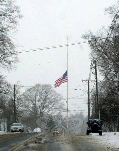 Newtown's Main Street flagpole was joined by countless others across town and the state last Saturday when its flag was lowered to honor those killed one year earlier, on 12/14. A number of memorial services were scheduled by houses of worship in Newtown on December 14, and other groups had also planned special events to coincide with the first anniversary of the shootings that ended with the death of 28 residents. A snowstorm that arrived in the area early Saturday morning meant many people went out for the early services or events, or just to complete some weekend errands. Most roads — and the entire town — were very quiet by Saturday afternoon. (Hicks photo)
