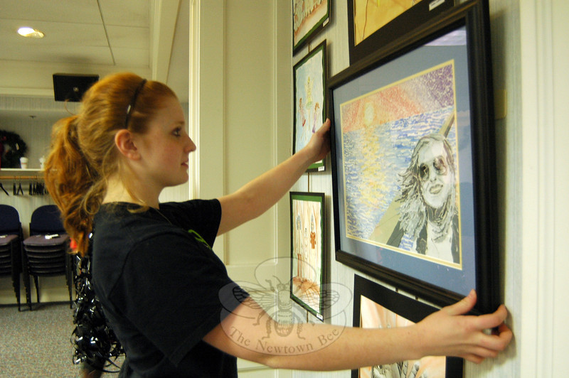 Newtown High School Advanced Placement Portfolio student Emma Sullivan hung one of her art pieces on the wall of the meeting room at C.H. Booth Library on Friday, December 13. She is one of ten students displaying art work in the space until Friday, December 20. (Hallabeck photo)