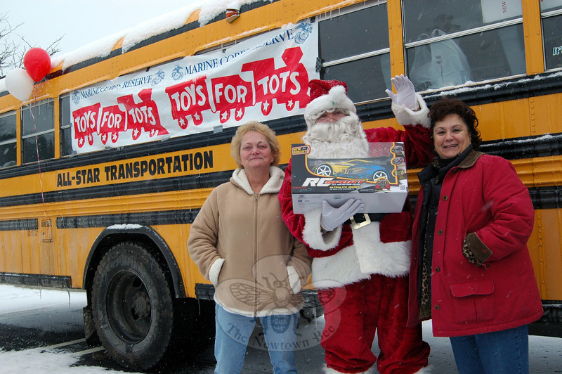 All-Star Transportation, which provides bus services to the Newtown School System, hosted a Stuff-A-Bus event Saturday, December 14, to collect for Toys For Tots. Santa Claus stood with Joan Baumgart, left, and Linda Nasse, right, between collecting toys from people stopping by Sandy Hill Plaza. Channel 8 Traffic Reporter Teresa Labarbera visited during the event. All the toys collected were delivered to the Toys For Tots center in Ridgefield. (Hallabeck photo)