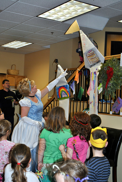 Cinderella admires the paper castle drawn by children attending the Royal Party, pointing out the banner at the top. (Crevier photo)