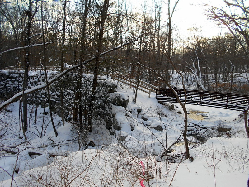 Along the trail at the Orchard Hill Nature Preserve is a foot bridge crossing a brook that runs below a sturdy stone wall, partially seen to the left. (Bobowick photo)