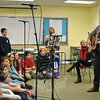 "Alternate Routes band member Tim Warren, who along with Eric Donnelly composed the song ""Nothing More,"" performs for chorus students at a special rehearsal Tuesday, November 26. Linda Sobo, composer of another piece the students will perform in January, looks on.	(Crevier photo)"