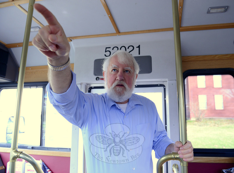 Dan Cruson points out the window during the trolley tour to alert guests to architectural features of homes they pass on Main Street during the 28th Annual Holiday Festival. (Bobowick photo)