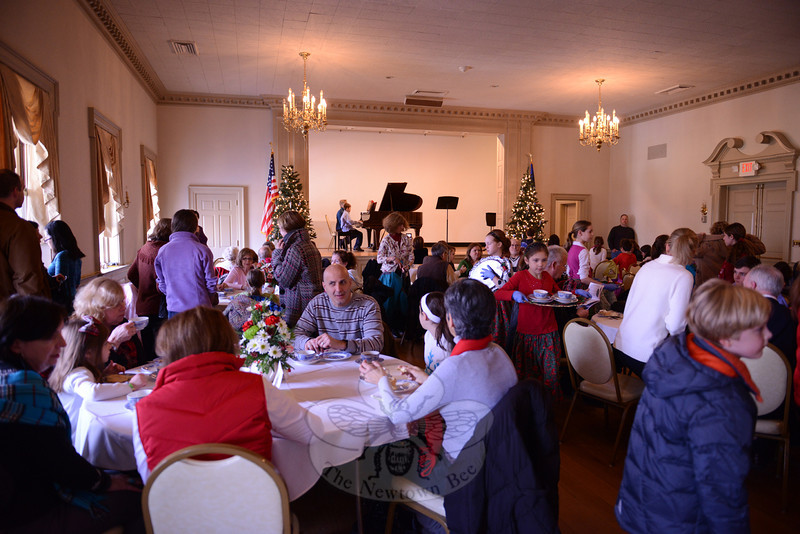 Carrying a tray with two empty tea cups through the crowded room, Sophie Satmary, center, lends a hand during the Victorian Tea during the 28th Annual Holiday Festival. (Bobowick photo)