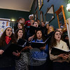 The Newtown High School Singers line the stairs in the C.H. Booth Library entrance, greeting guests to carols, during the 28th Annual Holiday Festival. (Bobowick photo)