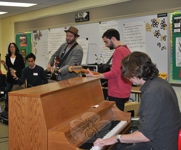RIS choral instructor Michelle Tenenbaum, far left, directs as Alternate Routes band members Kurt Leon, percussion, Tim Warren, guitar and vocals, Ian Tait, bass, and Eric Donnelly, piano, perform. The band was at the intermediate school November 26 to rehearse with students for the January winter concert, in which Alternate Routes will take part. (Crevier photo)