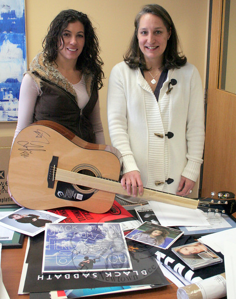 Stephanie Cinque, founder of The Resiliency Center of Newtown (RCN), and Beth Bogdan, who organized two Music For Newtown auctions, on February 1. The women were packaging the items that had sold during Ms Bogdan's second annual auction, which this year served as a fundraiser for RCN. Ms Bogdan is holding a guitar signed by the members of Florida Georgia Line. (Hicks photo)