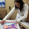 Beth Bogdan unrolls the Pearl Jam poster designed for the band's show in Hartford in October 2013. Signed by all members of the band, the poster was the highest grossing lot in the second Music For Newtown auction. (Hicks photo)