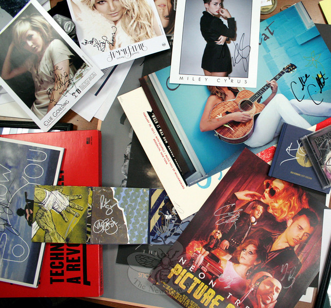 Nearly 50 lots were offered in the second Music For Newtown auction. Among them were, clockwise from upper left, signed photographs of Ellie Goulding, Britney Spears, and Miley Cyrus; an autographed Colbie Caillat poster and (hidden) a copy of her Breakthrough CD; signed CDs by Selema Gomez and Ben Howard; a Neon Trees autographed poster; a signed copy of the Bon Jovi CD What About Now; and a Jack Johnson autographed copy of From Here To Now To You on vinyl. (Hicks photo)