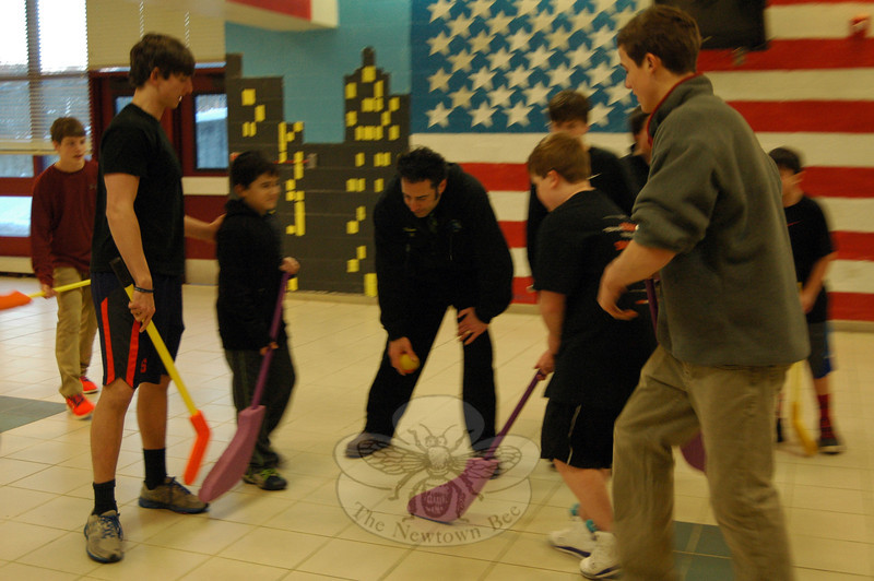"Newtown High School Guidance Counselor and REACH advisor Jeff Tolson drops the foam puck for a ""USA vs Russia"" hockey game, played with foam sticks, on Monday February 10. (Hallabeck photo)"