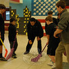 """Newtown High School Guidance Counselor and REACH advisor Jeff Tolson drops the foam puck for a """"USA vs Russia"""" hockey game, played with foam sticks, on Monday February 10. (Hallabeck photo)"""