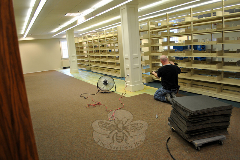 Mike Debarnado of Red Baron Carpet lays the last rows of carpet tiles in the Fiction Department of C.H. Booth Library, Wednesday, February 19. (Crevier photo)