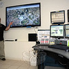 Tom Ramsdell, a dispatcher at the Newtown Emergency Communications Center (NECC) at Town Hall South, points to a large flat panel display that has been installed at NECC to aid in the dis-patching of police, fire, and ambulance calls. The monitor displays an aerial photo of the southern end of Main Street.  (Gorosko photo)