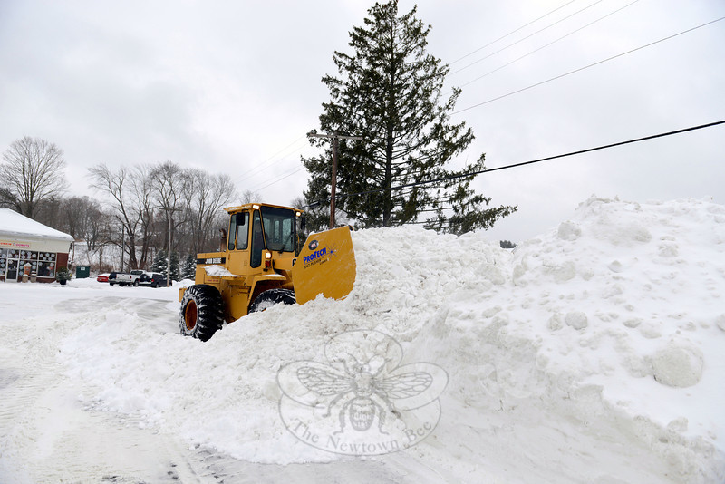 Ryan Clark used a loader to move mounds of snow at Queen Street Shopping Center last week. A slow and steady storm that began just before dawn on February 13 blanketed the day with a half foot or more of snow. By late evening the skies dropped hard rain, then snow again through the early hours of February 14. (Bobowick photo)
