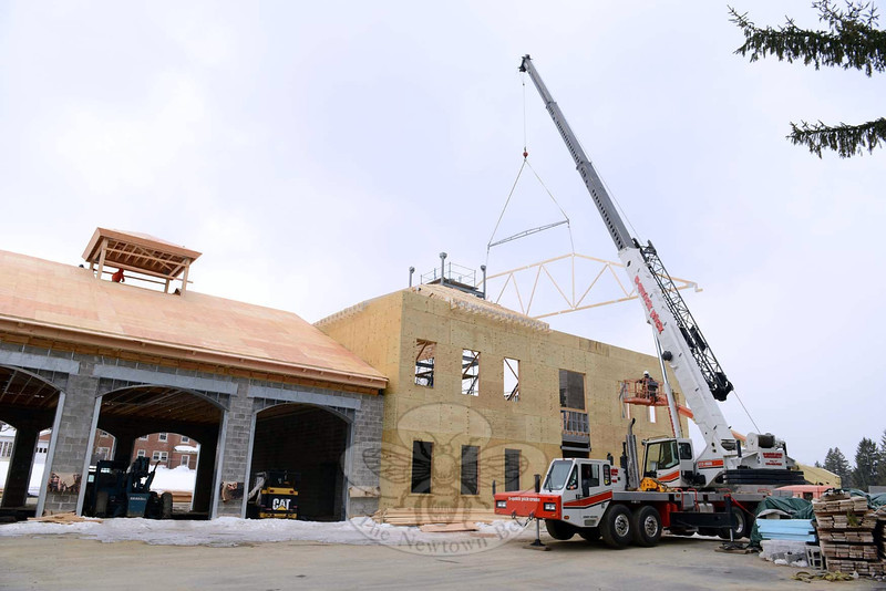 At the site that will serve as the headquarters for Newtown Volunteer Ambulance Corps, dangling from a crane is the triangular roof truss falling into place as men in a bucket lift, right, watch its progress on Wednesday, February 26. Other construction members are visible in the cupola, left. (Bobowick photo)