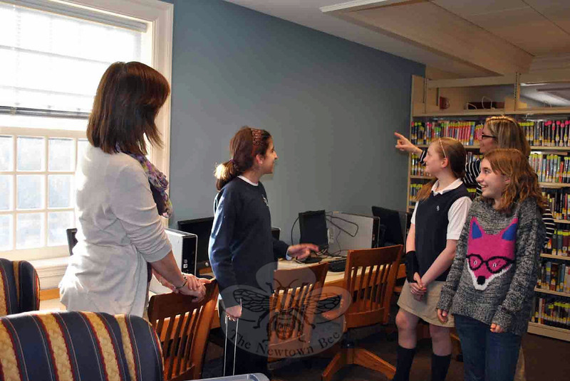 Samantha Kohler, far right, art teacher at St Rose and muralist, points to the wall in the Young Adult section of the C.H. Booth Library that will be painted with a mural. Young Adult Council (YAC) members, from left, Maya Welber, Caroline Palmer, and Hailey Pankow offer suggestions, while YAC advisor Kim Weber looks on.	(Crevier photo)
