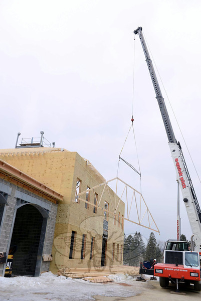 A fully extended crane arm hauls roofing sections into place Wednesday, February 26, at the site that will serve as the headquarter for Newtown Volunteer Ambulance Corps. (Bobowick photo)