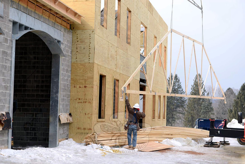A crewman from Nosal Builders Inc steadies the corner of a roof truss as a crane lifts it into place at the site that will serve as the headquarters for Newtown Volunteer Ambulance Corps. (Bobowick photo)