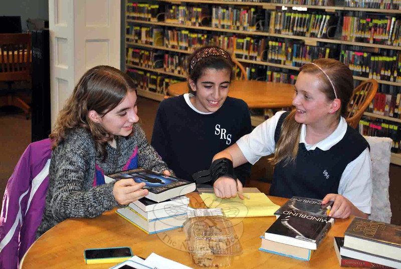 From left, YAC members Hailey Palmer, Maya Welber, and Caroline Palmer discuss ideas for the upcoming Battle of the Books, and ways to raise funds to support the Young Adult Department. (Cre-vier photo)
