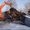 A worker used an excavator this week to demolish a deteriorated 2,840-square-foot structure at 57 Church Hill Road that formerly was occupied by Apex Glass. Town officials considered the vacant building to be a case of blight and employed the town's recently enacted anti-blight ordinance to have the owner to remove the structure. (R. Scudder Smith photo)