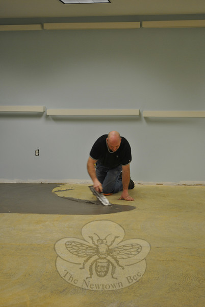 Mike DiBenardo of Red Baron Carpet in Newtown puts down a layer of adhesive in the Children's Department of the C.H. Booth Library Tuesday morning, February 4. Sections of the Children's Department will have vinyl tiles, and the main space will be carpeted. (Crevier photo)