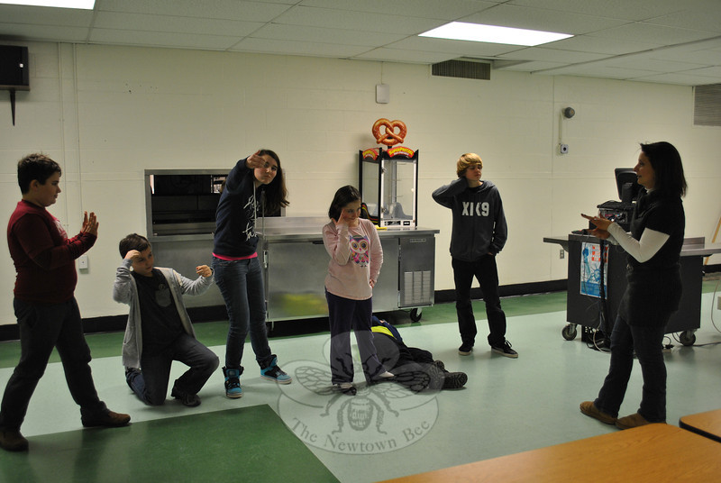 Theresa Talluto, far right, prompts students in her Theatre On Your Feet improvisational Theatre program, as they freeze in place during an exercise. From left are Tristan Filiato, Bram Roberts, Caitlyn Child, Sarah Flynn, Jacob Hinden (on floor), and Carter Goodrich. (Crevier photo)