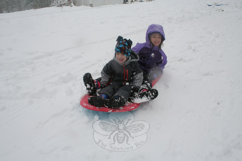 Sean and Isabelle Carol enjoyed the snow that arrived in Newtown before daybreak Monday, sledding in their front yard that afternoon. A storm that was to bring a few inches of snow to the region had dropped up to six inches in different areas of town by late afternoon. (Hicks photo)