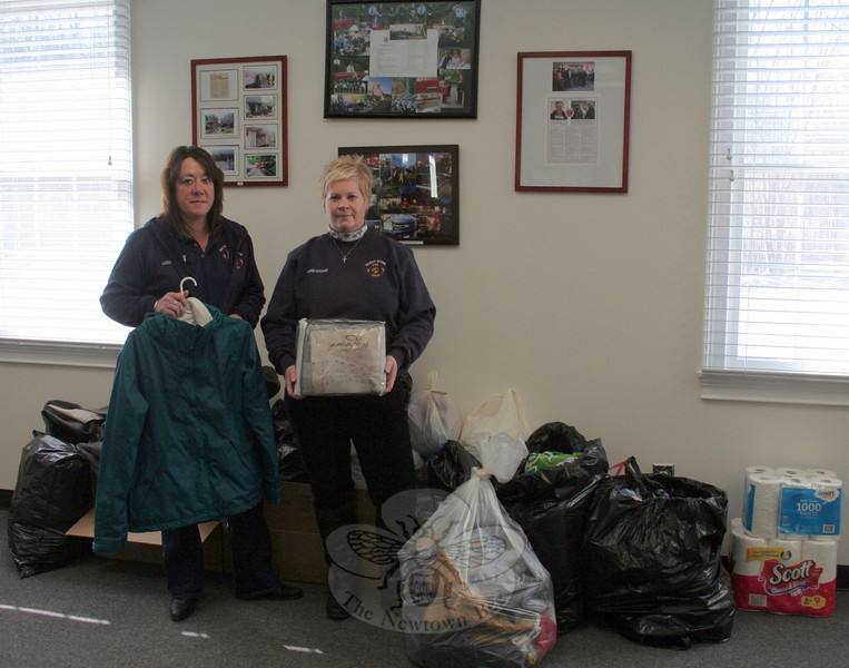 Sandy Hook Volunteer Fire & Rescue Ladies Auxiliary President Laurie Comerford, left, and Treasurer Sharon Doherty stand among some of the items that were donated by Newtown residents this week for those who were displaced by a major fire in Shelton on January 5–6. The ladies auxiliary will continue collecting nonperishable items until January 15. Clothing is no longer needed, but everything else to help rebuild homes for approximately 30 people would still be helpful, according to Shelton firefighters. (Hicks photo)