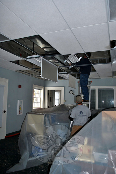 Workers from J.P MaGuire Associates,  property damage remediation specialists, remove damaged tiles and insulation from the ceiling of the tech area on the main floor of the C.H. Booth Library, Sunday morning. Frozen pipes burst Saturday afternoon, flooding an extensive section of the library.