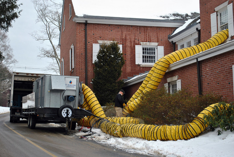 Huge hoses connect the mobile dry unit to various sections of the C.H. Booth Library, Sunday, January 5, in an effort to extract water from the carpeting affected by flooding the previous day. J.P. MaGuire Associates is handling the remediation. (Crevier photo)