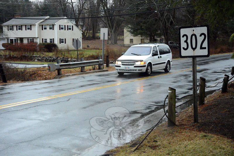 The state Department of Transportation has scheduled an informational meeting in Newtown for February 11 on its plans to build a new bridge and increase the pavement width on Sugar Street (Route 302), just west of its intersection with Main Street, South Main Street, and Glover Avenue. This view from the north side of Sugar Street looks southwestward toward the bridge that will be widened. Elm Drive is in the background, behind a short section of guardrailing that stands alongside the short Sugar Street bridge. (Gorosko photo)