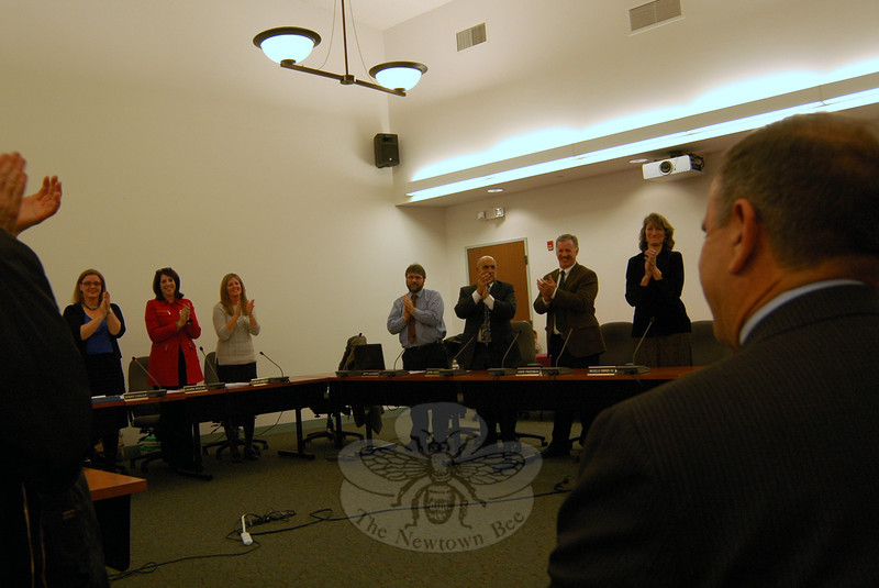 Members of the Board of Education stood and applauded to welcome Dr Joseph Erardi, Jr, facing the board far right, after the board unanimously voted to accept him as the school district's new superintendent. School board members from left are Chair Debbie Leidlein, Vice Chair Laura Roche, Secretary Kathy Hamilton, Keith Alexander, John Vouros, David Freedman, and Michelle Ku. (Hallabeck photo)