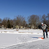 """Cutting a solo figure across Hawley Pond, Huntington resident Steve Ballok pushed a shovel up and down an ever-widening clearing on the ice Wednesday. In town for a guitar lesson with local teacher Jim Allyn, Mr Ballok stopped his truck along Elm Drive, tied on his skates, and started shoveling. Why? """"Kids will be by later,"""" he said. (Bobowick photo)"""