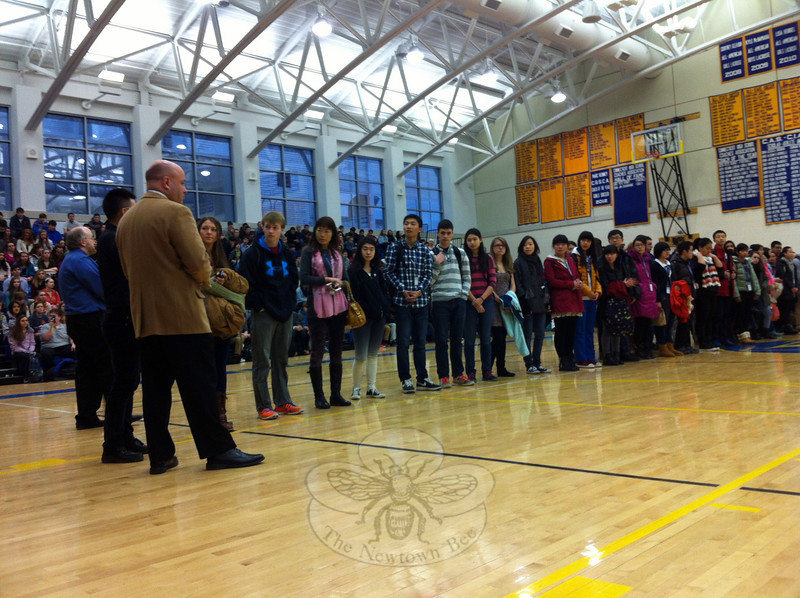 Newtown High School Principal Charles Dumais, front left, greeted a visiting delegation from China during a morning pep rally at NHS on Monday, January 27. (Hallabeck photo)