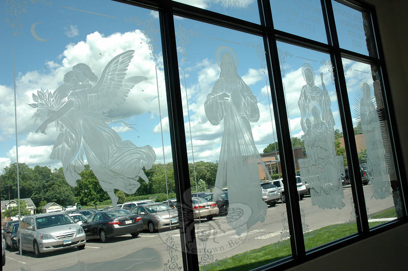 Adrienne Keogler designed the decorations of the front windows of St Rose of Lima's Holy Innocents Faith Formation Center before passing her designs on to an artist for creation, according to St Rose of Lima's Monsignor Robert Weiss. (Hallabeck photo)