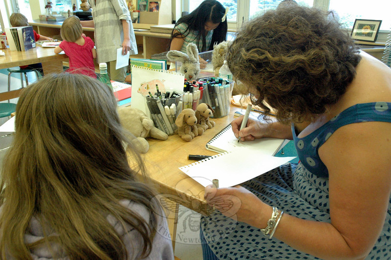Caitlin Ferrell, left, looked on as author and illustrator Karen Romano Young drew two of Caitlin's stuffed animals, Mel, left, and Little Brown Pup.