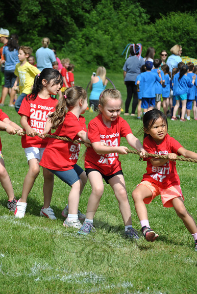"""Head O' Meadow School held its Spirit Day on Friday, June 6. school pride was evident, from hair dyed to match class T-shirts, to painted faces and colorful wigs, and a hillside painted to read """"There's No Place Like HOM!"""" As grades kindergarten through four thronged the playing field behind the school, ready to take part in the ten fun events set up by dozens of parent volunteers, Coach Steve Dreger took a moment to explain the significance of the day. Along with challenging the children physically, Spirit Day """"is meant to promote school spirit, togetherness, unity, and love,"""" said Coach Dreger. (Crevier photo)"""