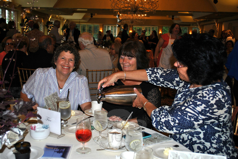 Suzanne White, right, pours coffee for Marsha Moskowitz, left, and Debbie Vaughan. The women were guests at a table hosted by Joanne's Fitness Studio. (Crevier photo)