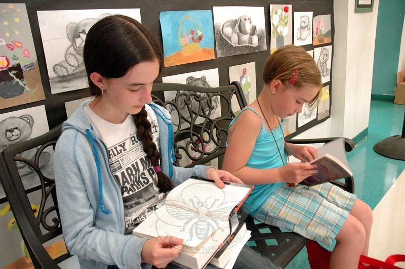 Sisters Stephanie, left, and Taylor Cobb used a break between activities at this year's New Stories for Newtown to read. Stephanie read Tony DiTerlizzi's The Battle for WondLa, and Taylor read Gail Carson Levine's Writing Magic.