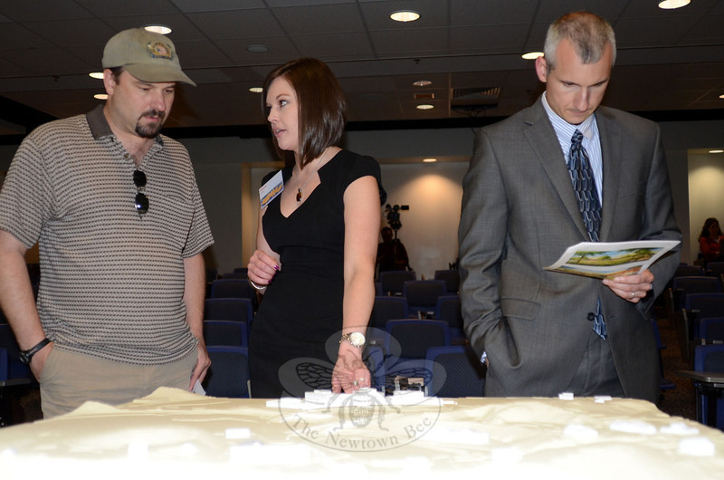 Newtown resident Chris Cook, left, and Alana Konefal of Svigals + Partners discuss one of the aspects of a Sandy Hook School model on display at a community information forum on the project held June 5 in the high school lecture hall. Resident and Sandy Hook parent Steve Uhde also attended and is pictured reviewing architectural material provided by the design team. (Voket photo)