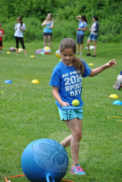 Second grade student McKenzie Roszman concentrates on not dropping the tennis ball from the paddle as she circles the bouncy ball, part of the Spirit Day obstacle course. (Crevier photo)