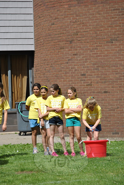 "Head O' Meadow School held its Spirit Day on Friday, June 6. school pride was evident, from hair dyed to match class T-shirts, to painted faces and colorful wigs, and a hillside painted to read ""There's No Place Like HOM!"" As grades kindergarten through four thronged the playing field behind the school, ready to take part in the ten fun events set up by dozens of parent volunteers, Coach Steve Dreger took a moment to explain the significance of the day. Along with challenging the children physically, Spirit Day ""is meant to promote school spirit, togetherness, unity, and love,"" said Coach Dreger. (Crevier photo)"