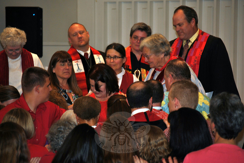 Clergy, friends, family, and congregants lay hands on Allysa De Wolf, center, an integral piece of the UCC ordination ceremony. (Crevier photo)