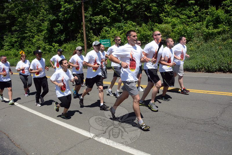 Newtown Police Department members and Garner Correctional Institution staff participated on June 6 in the Special Olympics of Connecticut Torch Run to show their support for the Special Olympics, which were held that weekend in New Haven and Hamden. The runners are shown on Dodgingtown Road (Route 302) near its intersection with Hattertown Road. Seen running in the front row, from left, are Newtown police officers Matthew Wood, William Chapman (carrying torch), Steven Siecienski, and John McDermott.  (Gorosko photo)
