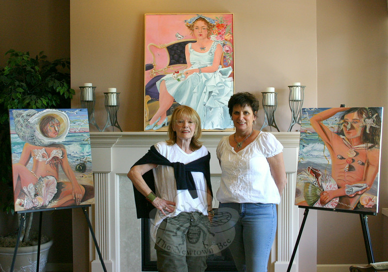 """Artist Susan McLaughlin (left) stands with Melanie Allen, the owner of Avancé Esthétiques, inside the Sand Hill Plaza day spa on Monday, June 16, shortly after a collection nearly two dozen of her works were put on view. The exhibition, """"Natural Beauty,"""" is on view until July 12. It is part of The Society of Creative Arts of Newtown's ongoing """"Art About Town"""" exhibition series. The work on the left is called """"Roxanne,"""" the work on the right is """"Cyrano,"""" and together they are """"The Beach Combers."""" Above the mantel is another of Ms McLaughlin's works, """"Alice's Aura.""""  (Hicks photo)"""