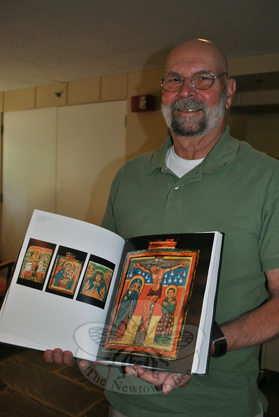 Friends of the C.H. Booth Library book expert John Renjilian holds a copy of an art book of Ethiopian icons, one of more than 120,000 items expected to be offered during the 39th Annual Friends of C.H. Booth Library Book Sale, July 12-16.  (Crevier photo)