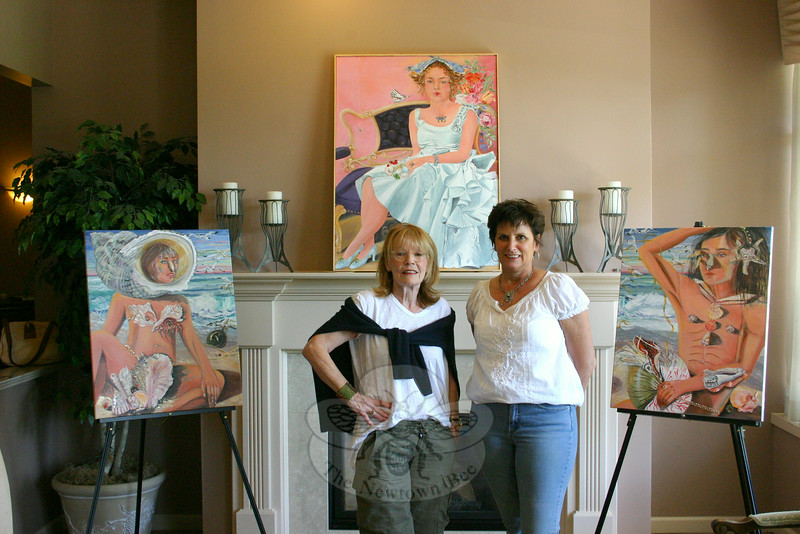 "Artist Susan McLaughlin (left) stands with Melanie Allen, the owner of Avancé Esthétiques, inside the Sand Hill Plaza day spa on Monday, June 16, shortly after a collection nearly two dozen of her works were put on view. The exhibition, ""Natural Beauty,"" is on view until July 12. It is part of The Society of Creative Arts of Newtown's ongoing ""Art About Town"" exhibition series. The work on the left is called ""Roxanne,"" the work on the right is ""Cyrano,"" and together they are ""The Beach Combers."" Above the mantel is another of Ms McLaughlin's works, ""Alice's Aura.""  (Hicks photo)"