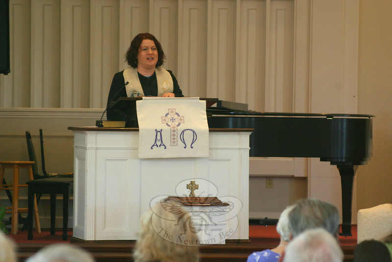 """It was a bittersweet service at Newtown Congregational Church on June 15, when Reverend Allysa De Wolf took to the pulpit to offer the morning's sermon. Ordained just one week earlier, Rev De Wolf was offering her first sermon as an ordained minister as well as her final while serving at NCC. Rev De Wolf has already been hired as pastor of First Congregational Church in Santa Barbara, Calif. On Sunday she delivered a message called """"The Great Commission,"""" filled with both laughter and a few tears, and promised that Sunday was """"not good-bye, but farewell for now … see you later … auf wiedersehen, adieu."""" Following a standing ovation, the Rev De Wolf asked those in attendance to make a circle around the sanctuary. Holding hands, members and their church leaders sang """"We've Come This Far By Faith"""" as the morning's closing hymn. A native Californian, Rev De Wolf does not begin her new commission until August, but she departed for the West Coast following Sunday's worship service.   (Hicks photo)"""