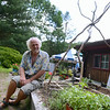Sticks and Stones Farm owner Tim Currier sits at the edge of a small garden where vegetables grow. The raised soil and plantings are an example of square foot gardening, which makes the most of small spaces.  (Bobowick photo)